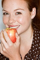 Young woman eating apple, smiling, close-up, portrait