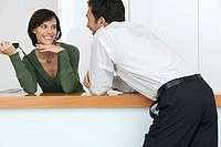 Businessman flirting with receptionist at reception desk, smiling, woman with telephone headset