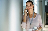 Businesswoman with identity card around neck standing in lobby using mobile phone, holding cup