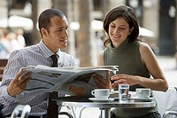 Couple sitting at pavement cafe table, businessman reading newspaper, woman looking on, smiling