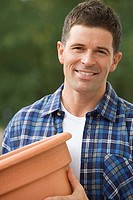 Man in checked shirt holding plant pot, smiling, close-up, portrait