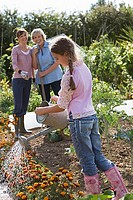 Girl 9-11 watering flowers in garden, mother and grandmother watching, smiling