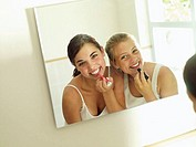 Teenage girls 15-17 applying make-up, reflection in mirror, smiling, rear view, portrait tilt