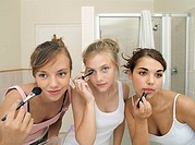 Three teenage girls 15-17 applying make-up in bathroom, front view, close-up