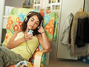 Teenage girl 15-17 sitting in armchair at home, listening to MP3 player, eyes closed tilt