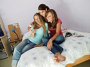 Three teenage girls 15-17 sitting on bed, using mobile camera phone, smiling tilt
