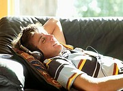 Teenage boy 15-17 relaxing on sofa, eyes closed, wearing headphones, smiling, side view (thumbnail)
