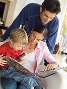 Family relaxing at home, boy 5-7 in mother's lap in chair, looking at photo album, close-up tilt