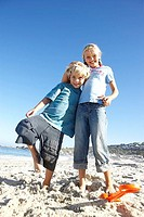 Boy 6-8 and girl 7-9 standing on beach, boy leaning on girl, smiling, portrait, low angle view