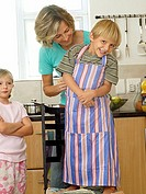 Mother and children 5-8 standing in kitchen, son 5-7 wearing striped apron, smiling, portrait