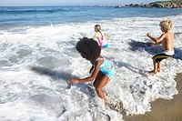 Three children 5-10 playing in surf on beach, rear view, sea in background