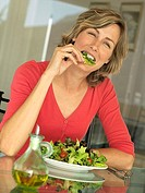 Woman eating fresh salad in kitchen, smiling, portrait tilt