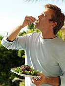Man eating fresh salad on veranda, profile