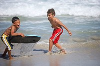 Two boys 7-9 in swimming shorts playing with bodyboard in surf on beach, laughing, side view