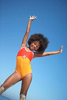 Girl 8-10 in orange swimsuit standing on beach, raising arms in air, smiling, portrait tilt