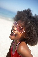 Girl 8-10 standing on beach in sunglasses, shouting, side view, portrait tilt
