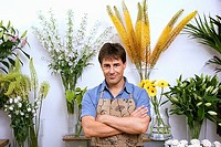 Male florist in apron standing in flower shop, arms folded, smiling, front view, portrait