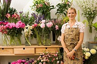 Florist in apron standing in front of display in flower shop, smiling, front view, portrait