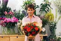 Man holding bouquet of flowers beside display in flower shop, smiling, front view, portrait