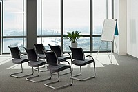 England, London, Canary Wharf, whiteboard and group of chairs beside window in empty conference room