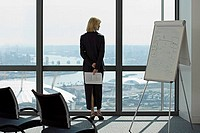England, London, Canary Wharf, businesswoman looking through window in conference room, rear view