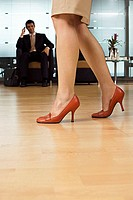 Businessman admiring woman in red stilettos, focus on legs in foreground, side view, surface level