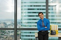 England, London, Canary Wharf, businessman standing beside office window, smiling, portrait