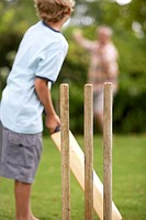 Grandfather and grandson 8-10 playing cricket, senior man bowling, focus on boy batting, rear view