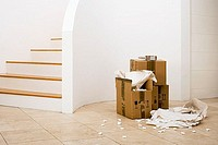 Small stack of boxes, paper and packing foam beside staircase in sparse room (thumbnail)