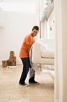 Man moving house, lifting white sofa wrapped in plastic sheet through doorway in sparse room