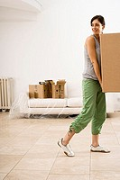 Woman moving house, carrying large cardboard box in sparse room, smiling, side view
