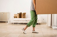 Woman moving house, carrying large cardboard box in sparse room, low section, profile