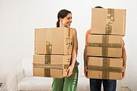 Couple moving house, carrying stack of cardboard boxes, man's face obscured, woman smiling