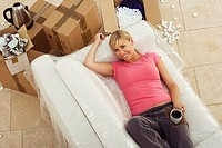 Woman moving house, lying on white sofa, taking tea break, smiling, portrait, overhead view