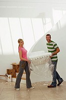 Couple moving house, carrying white chair wrapped in plastic sheet in room, smiling, portrait