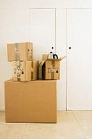 Stack of large and small sealed cardboard boxes in room, kettle in open box