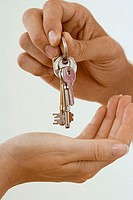 Man handing woman set of keys, close-up of hands, side view