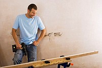 Man doing DIY at home, standing beside timber on workbench, holding power drill, smiling