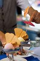 Waiter preparing ice cream desserts, adding cocktail umbrellas, close-up differential focus