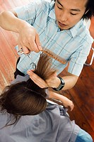 Young male hairdresser combing woman's hair in salon, close-up, overhead view