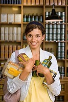 Female customer shopping in grocery store, holding groceries, smiling, front view, portrait