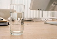 Glass of water on office desk, close-up