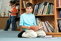 Boy 10-12 kneeling on floor beside bookshelf in library, holding book, smiling, portrait