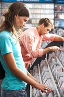 Young couple sifting through CDs in record shop, side view (thumbnail)