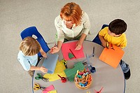 Two boys 4-6 making cards at desk in classroom, teacher assisting, overhead view