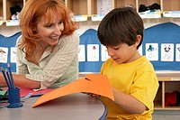 Boy 4-6 cutting piece of orange card at desk in classroom, teacher assisting, smiling