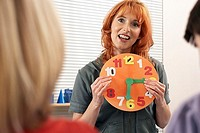 Two boys 4-6 learning to tell the time, focus on teacher holding colourful clock in classroom