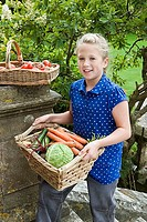 Girl 8-10 on garden steps carrying basket of vegetables, smiling, portrait, elevated view