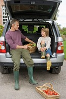 Father and son 8-10 sitting beside basket of fresh vegetables in car boot, smiling