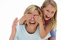 Girl 9-11 covering mother's eyes with hands, laughing, front view, portrait